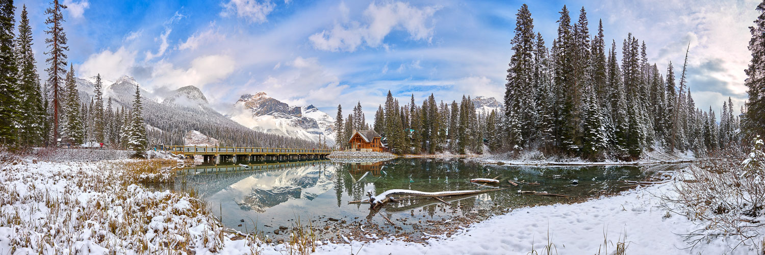 Snow-covered pines and mountains perfectly reflected in Emerald Lake, near Banff, Canada.