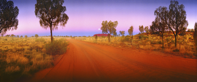 A red dirt road leading towards Uluru, NT, Australia.