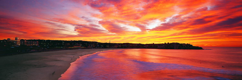 A brilliant red and orange sunrise over Bondi Beach, Sydney, NSW, Australia.
