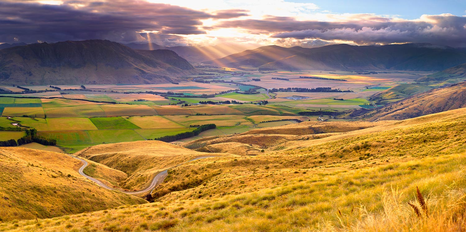 The golden rays of sunset breaking through clouds to light up the patchwork fields of the Nevis Valley, New Zealand.
