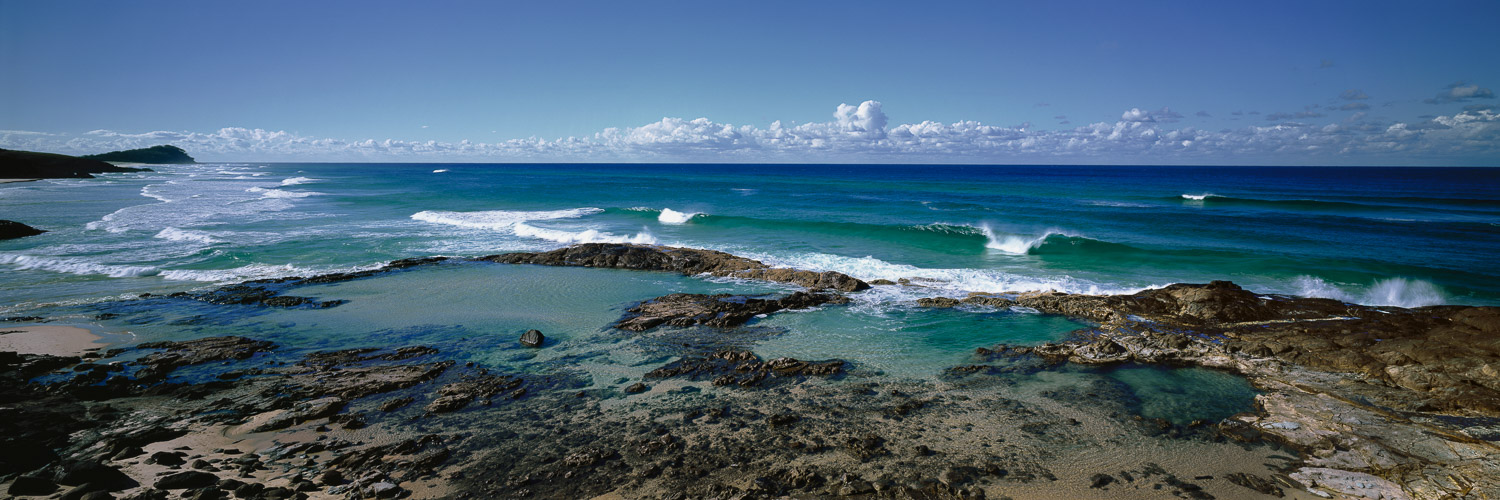White crested waves gently rolling into the beach at Champagne Pools, Fraser Island, Qld, Australia.