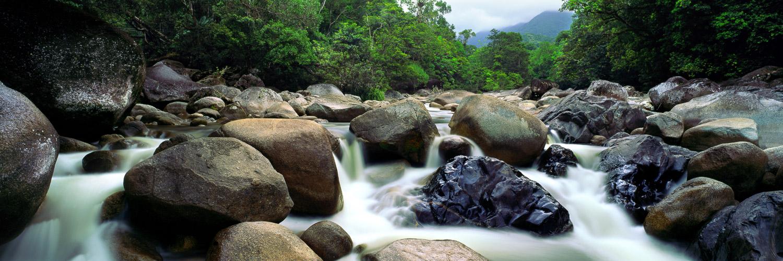 Mossman River flowing over boulders, through the rainforest, Qld, Australia.