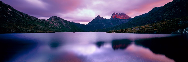 A shaft of dawn sunlight pierces the clouds above Dove Lake, Cradle Mountain, Tasmania, Australia.