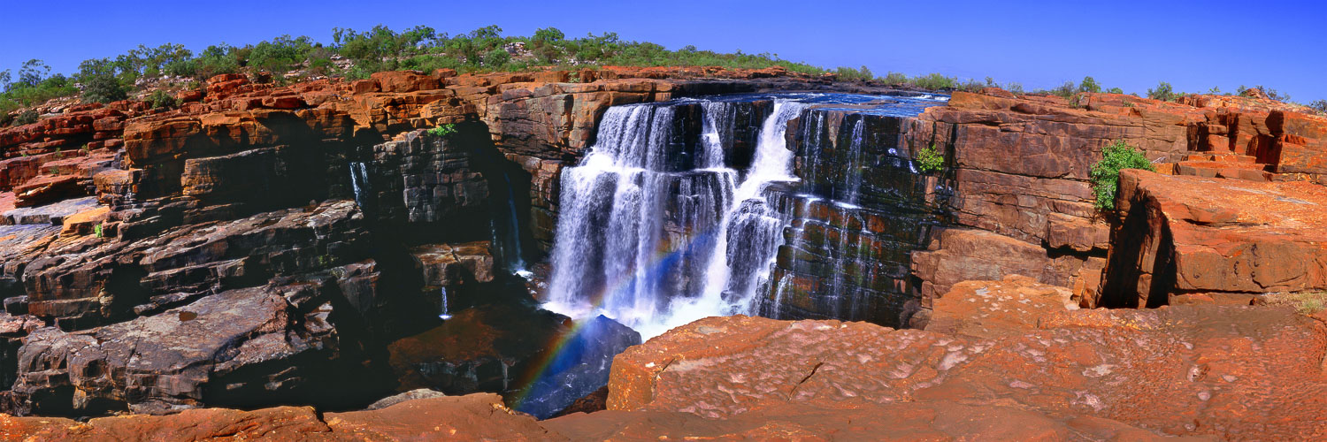 The cleansing waters of Mitchell Falls captured under a bright blue sky.