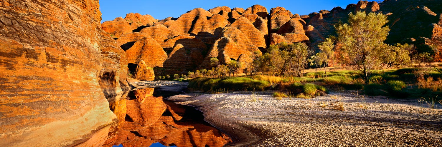 Early morning lights casting a golden glow over the domes of Purnululu National Park, Kimberleys, WA, Australia.