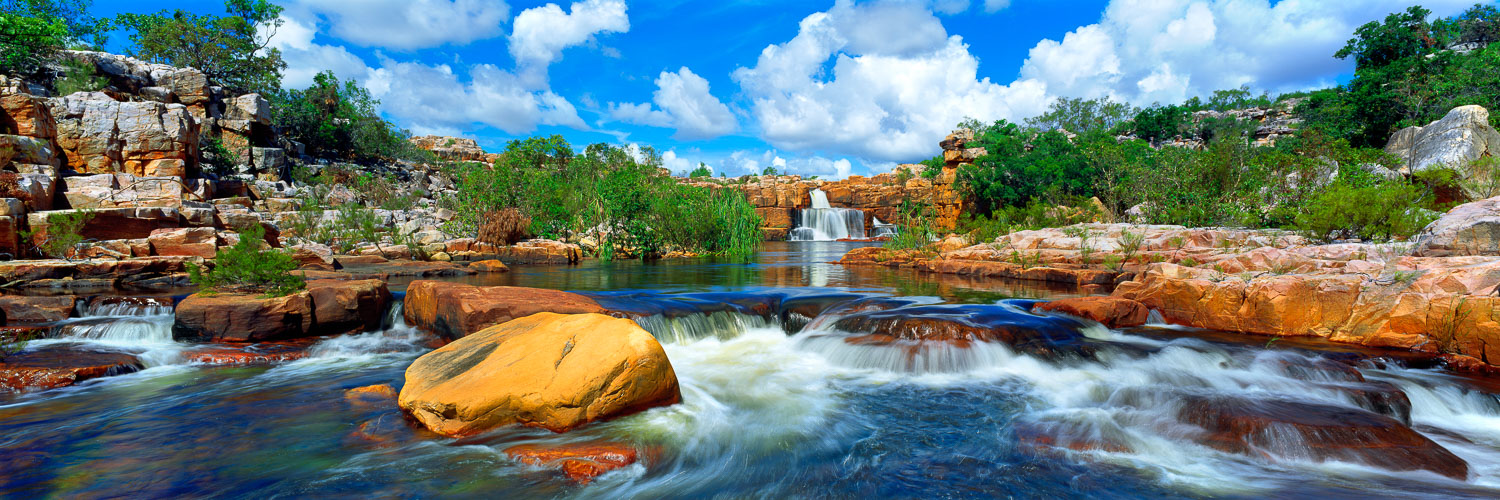 Clear blue skies are reflected in Atlantis Falls, flowing over ochre coloured boulders in the remote Kimberley region of Western Australia.