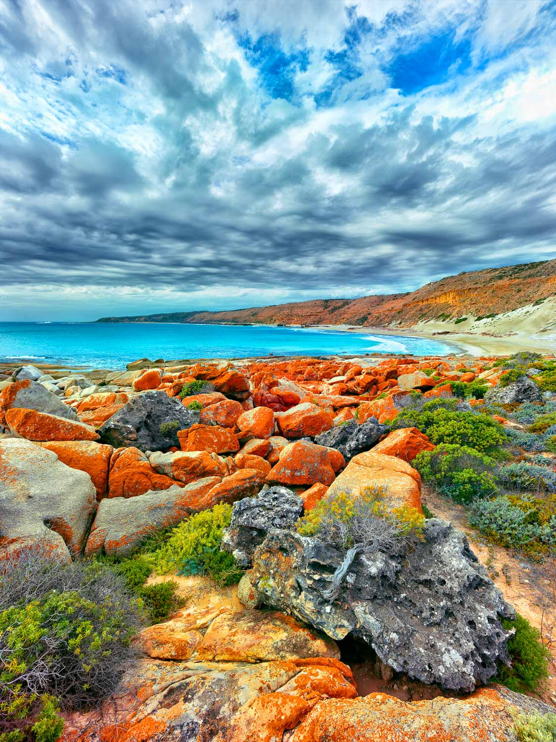 A pretty little coastal haven on the Eyre Peninsula with orange lichen on rocks in the foreground, South Australia.