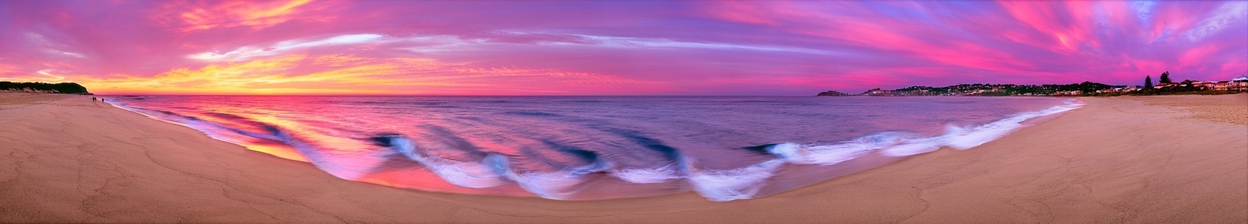 Bright pink panoramic sunrise off a central coast beach