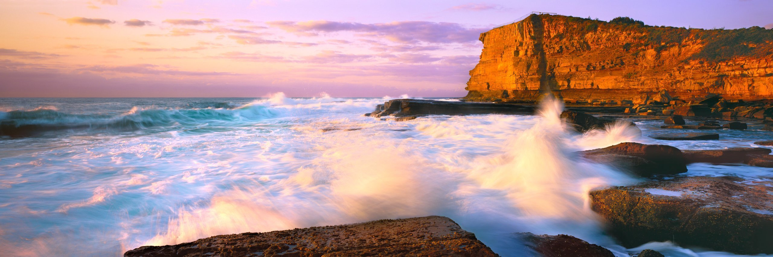 The Skillion Terrigal with waves crashing and the sun lighting up the rock face