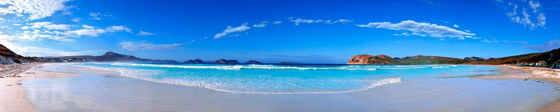 Gentle waves under a bright blue sky lap the shores of Cape Le Grand National Park, Western Australia.