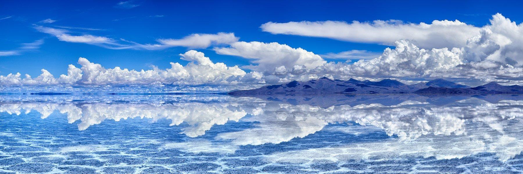 Fluffy white clouds perfectly reflected in Salar de Uyuni salt lake, Bolivia.