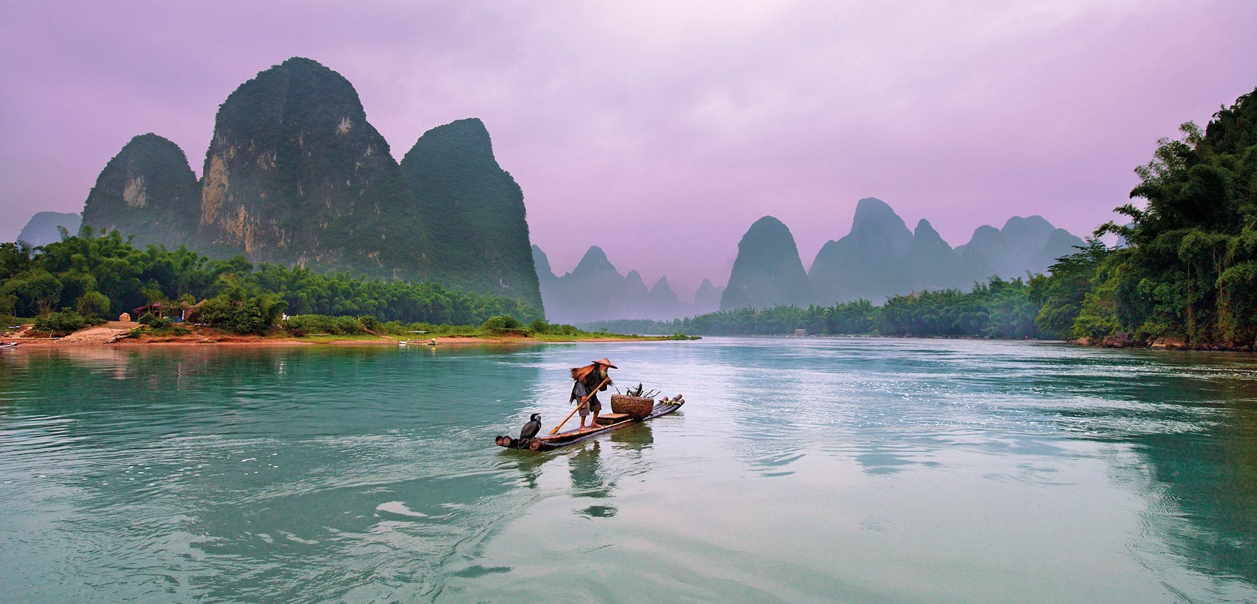 An old cormorant fisherman poling down the river on his raft, Guilin, China.