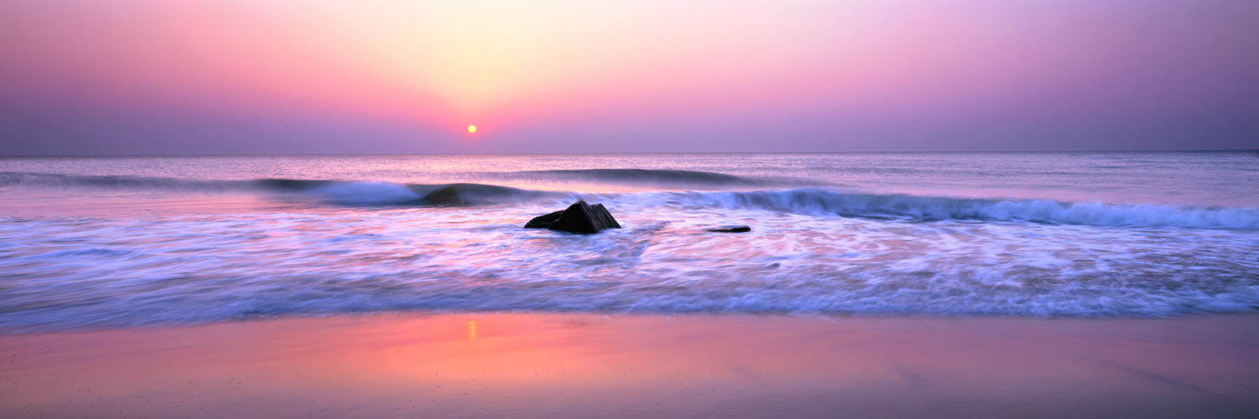 The rising sun, diffused by cloud, casting a magical pastel glow over Bethany Beach, Delaware, USA.