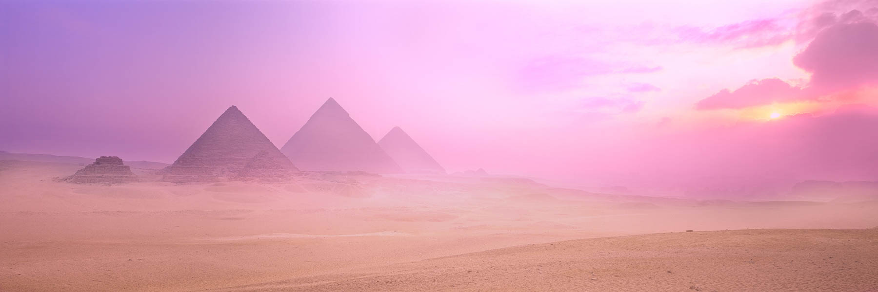Mist hanging low over the Great Pyramids of Giza at sunrise, Egypt.