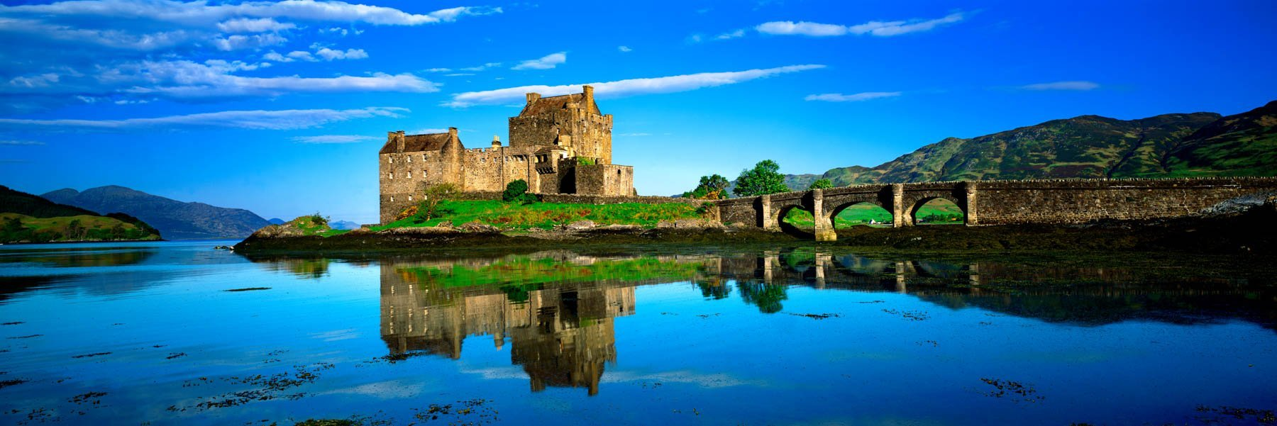 Perfect reflections of Eilean Donan castle in the clear blue lake, Scotland, UK.