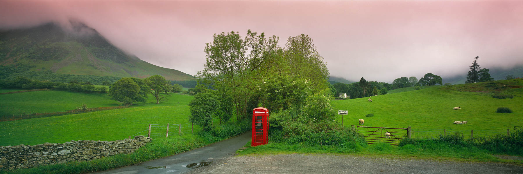 A red telephone box stands proudly amidst green fields in the Lakes District, England, UK.