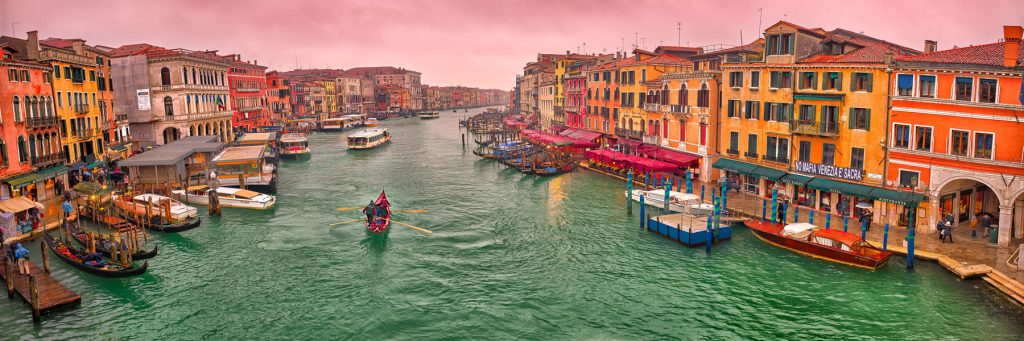 A romantic pastel twilight glow over boats and gondolas on The Grand Canal, Venice, Italy.
