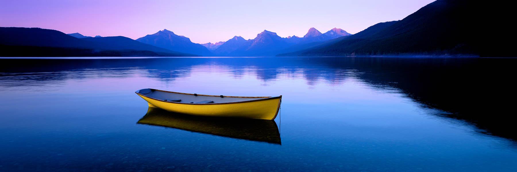 A solitary yellow canoe on Lake McDonald, Monana, USA.