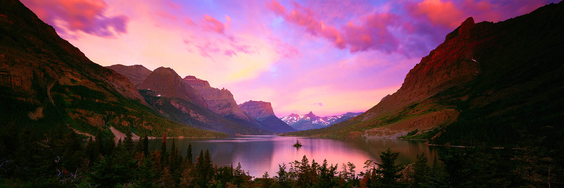 Sunrise casting glowing pink light across St Mary Lake, Glacier National Park, Montana, USA.