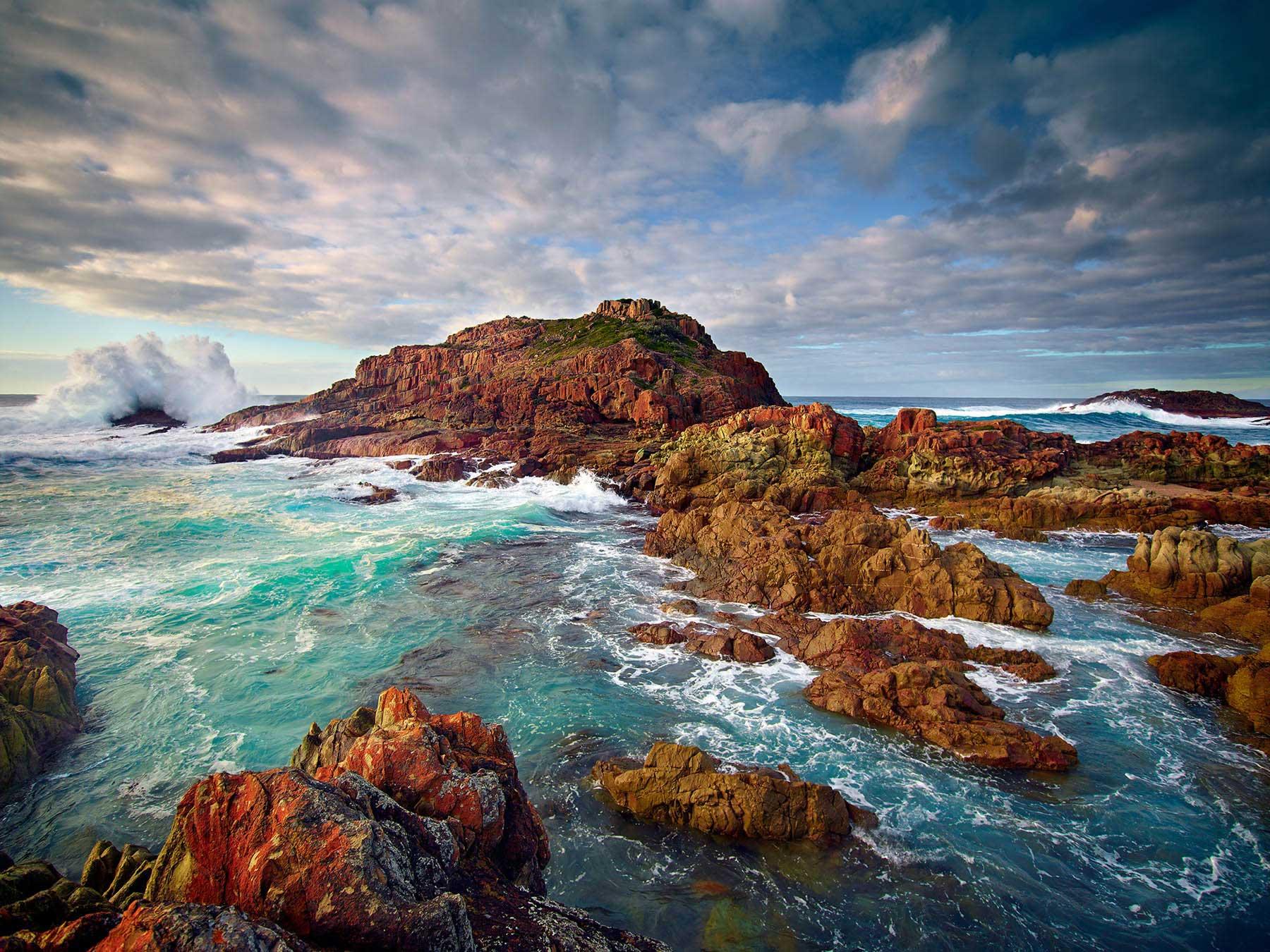Lichen covered rocks and pounding waves, Minmosa Rocks, NSW, Australia.
