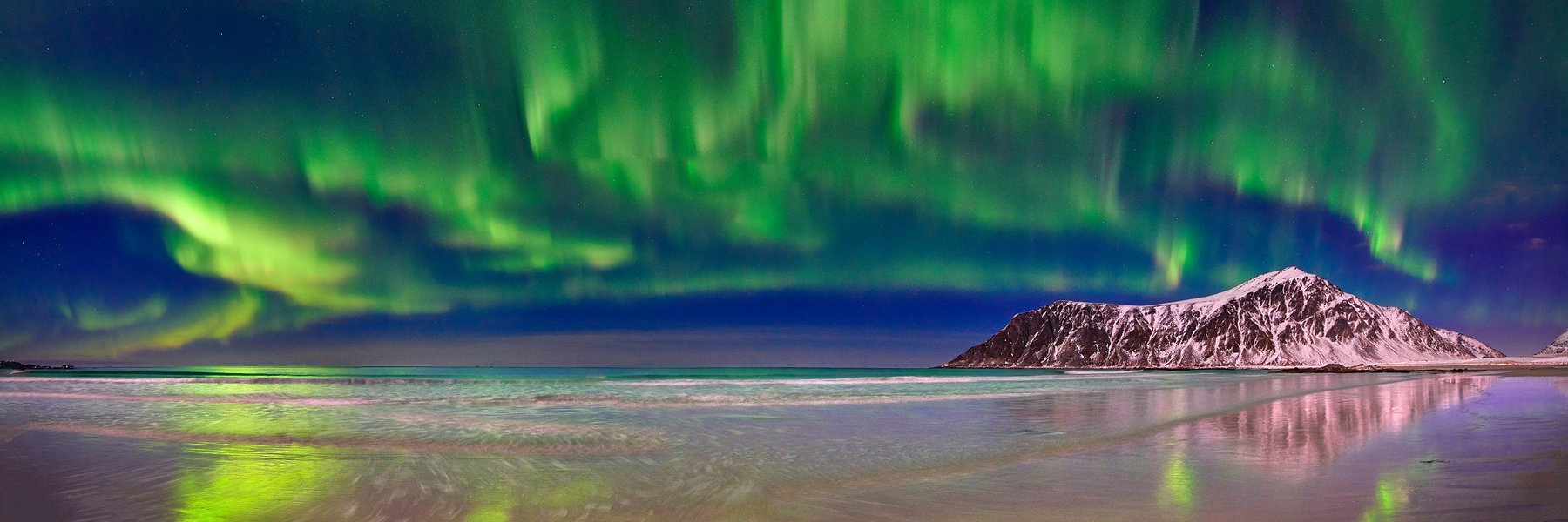 Brilliant green curtains of aurora borealis reflected in the waters on the shoreline, Lofoten Islands, Norway.