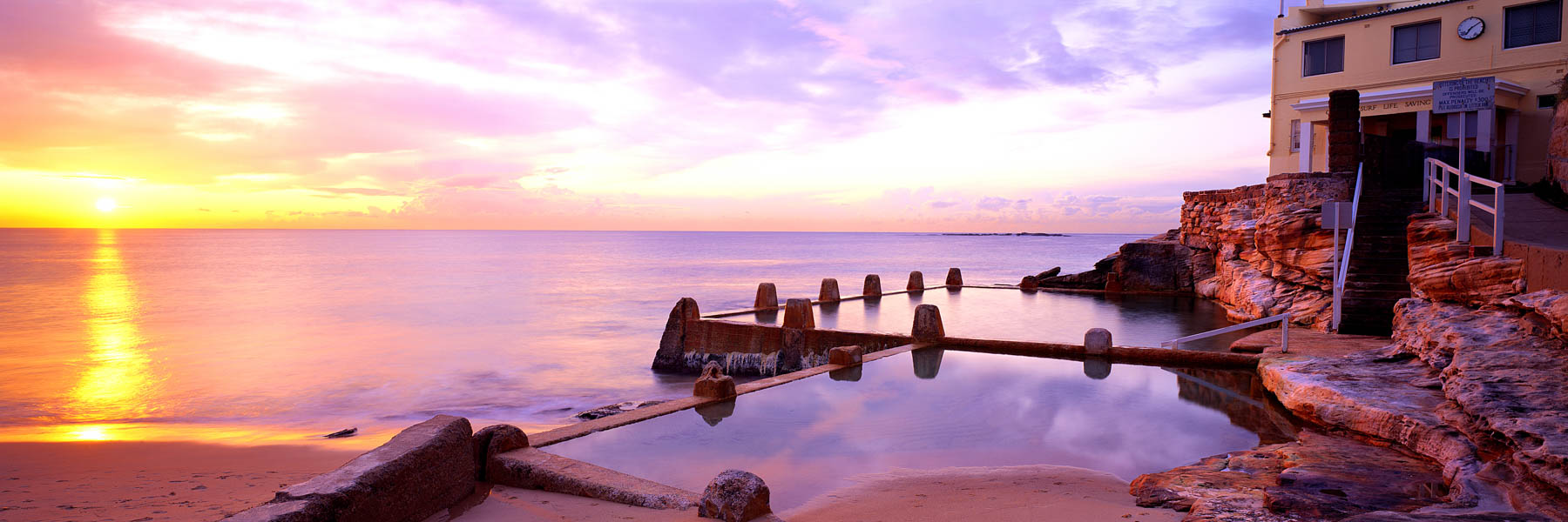Sunrise casting a golden and pastel glow over Coogee Sea Pool, Sydney, NSW, Australia.