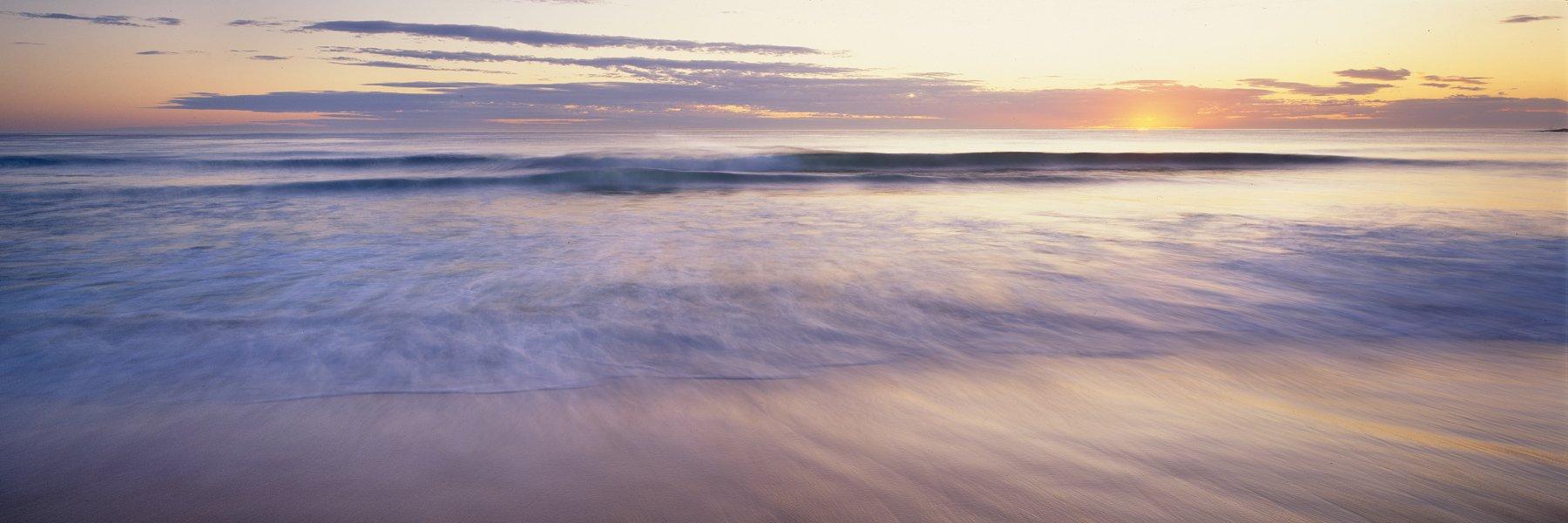 A pastel sunrise over a remote beach, NSW, Australia.
