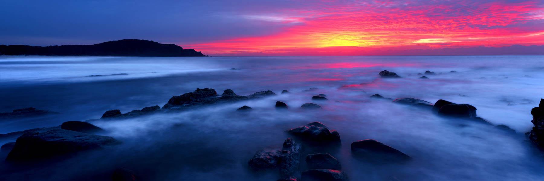 A vivid sunrise over Boomerang Beach, Pacific Palms, NSW, Australia.