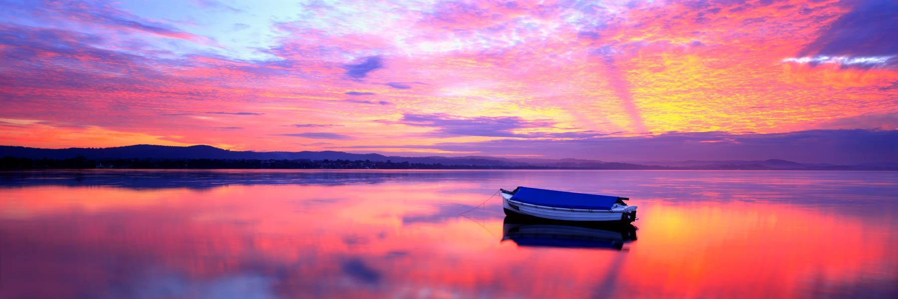 A glowing sunset over a small skiff on Tuggerah lakes, NSW, Australia.