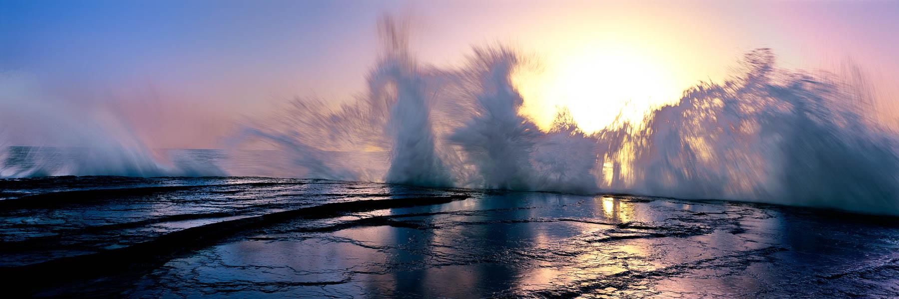 A wave smashing against the rock ledge at sunrise, Terrigal, Central Coast, Australia.