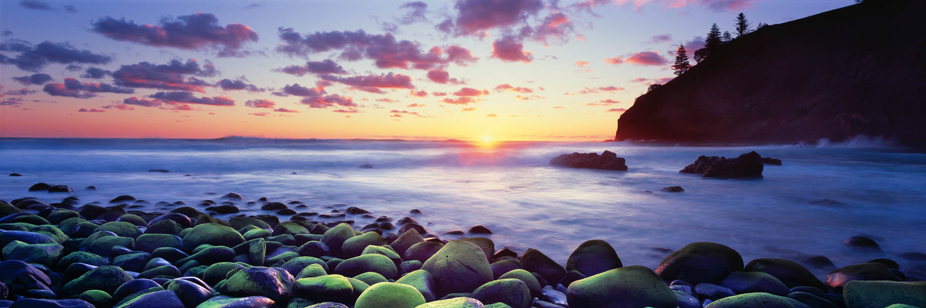 Sunset over soft waves and moss covered rocks in Anson Bay, Norfolk Island, Australia.