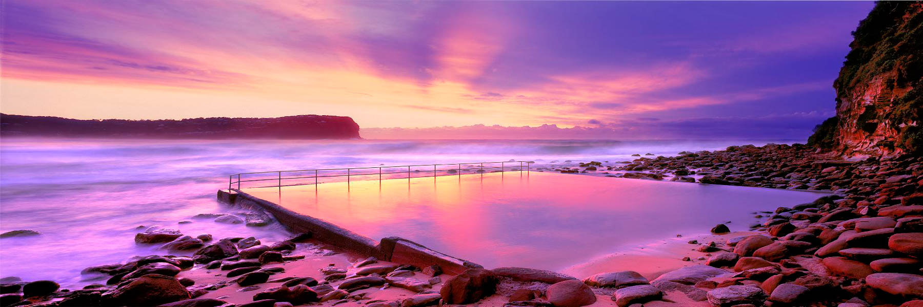 A gold and pastel sunrise reflecting in the sea pool, MacMasters Beach, Central Coast, NSW, Australia.