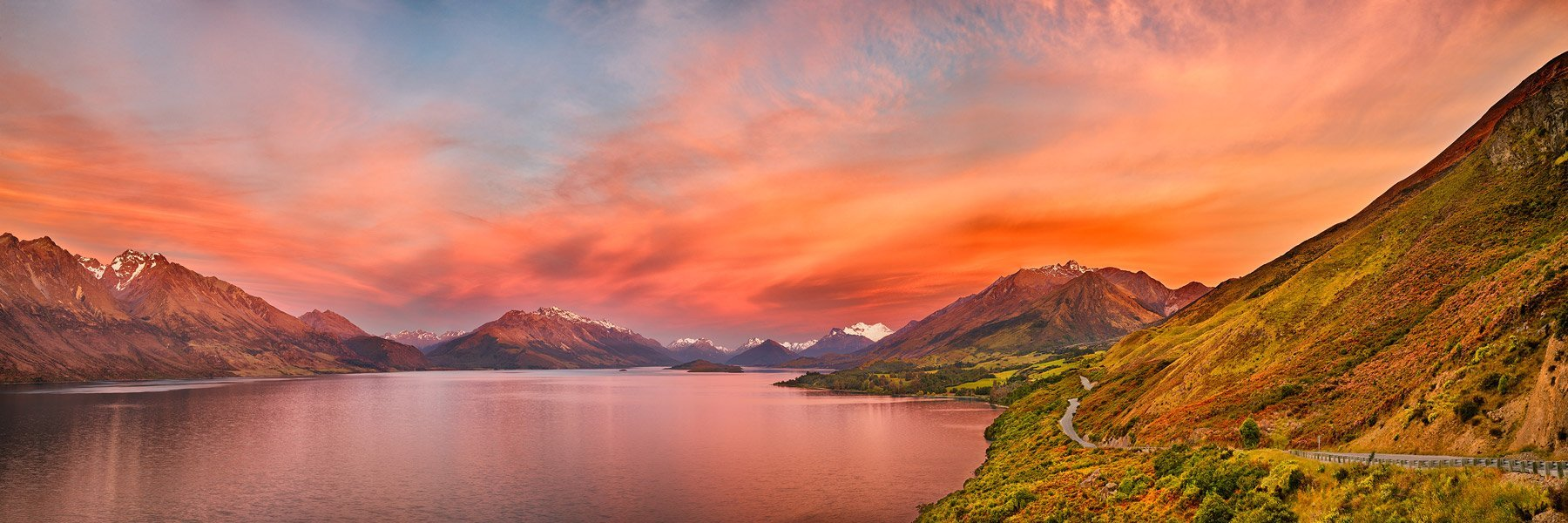 The setting sun igniting the sky with glorious amber hues, Lake Wakatipu, Queenstown, New Zealand.
