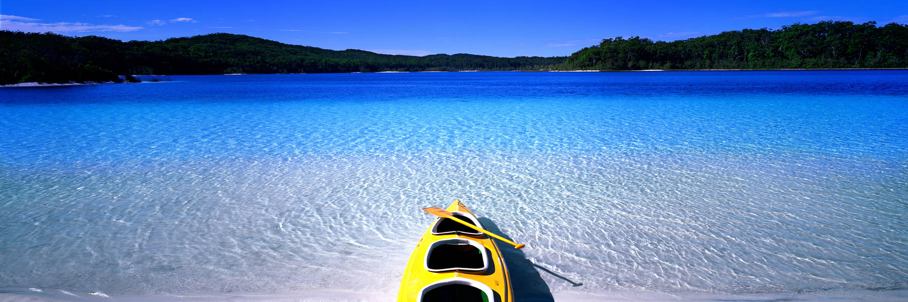 A bright yellow canoe on the shore of Lake Mackenzie, Fraser Island, ready for a grand adventure, Qld, Australia.