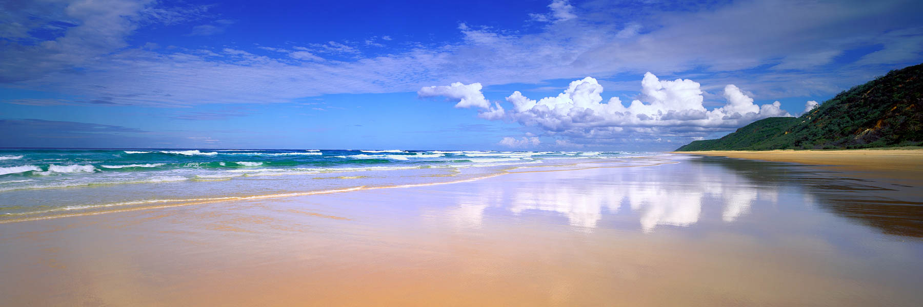 Blue skies and puffy clouds over Seventy Five Mile Beach, Fraser Island, Qld, Australia.