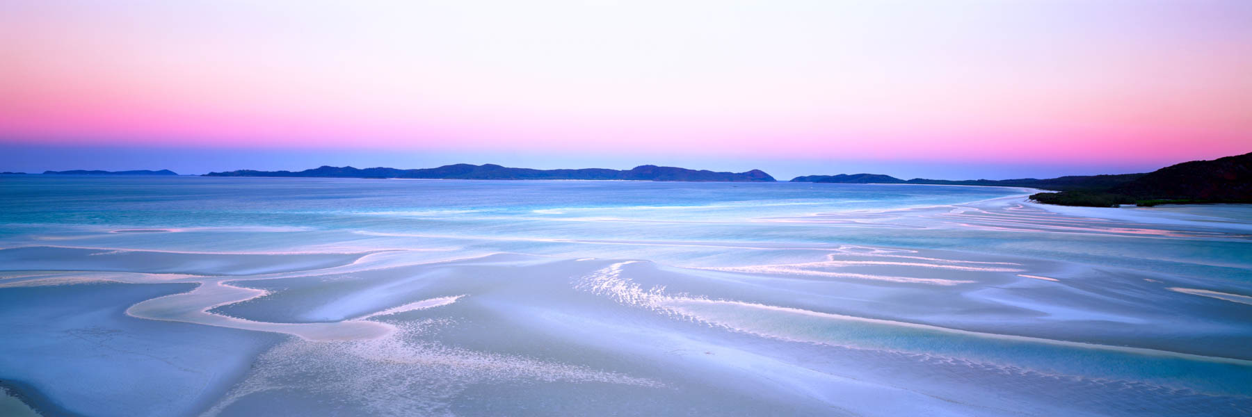 The pastel glow of sunset seems to transform the white sand of Hill Inlet into molten silver.