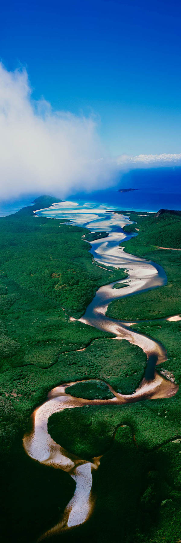 An aerial view of the tidal river flowing across Whitsunday Island towards Hill Inlet, Qld, Australia.