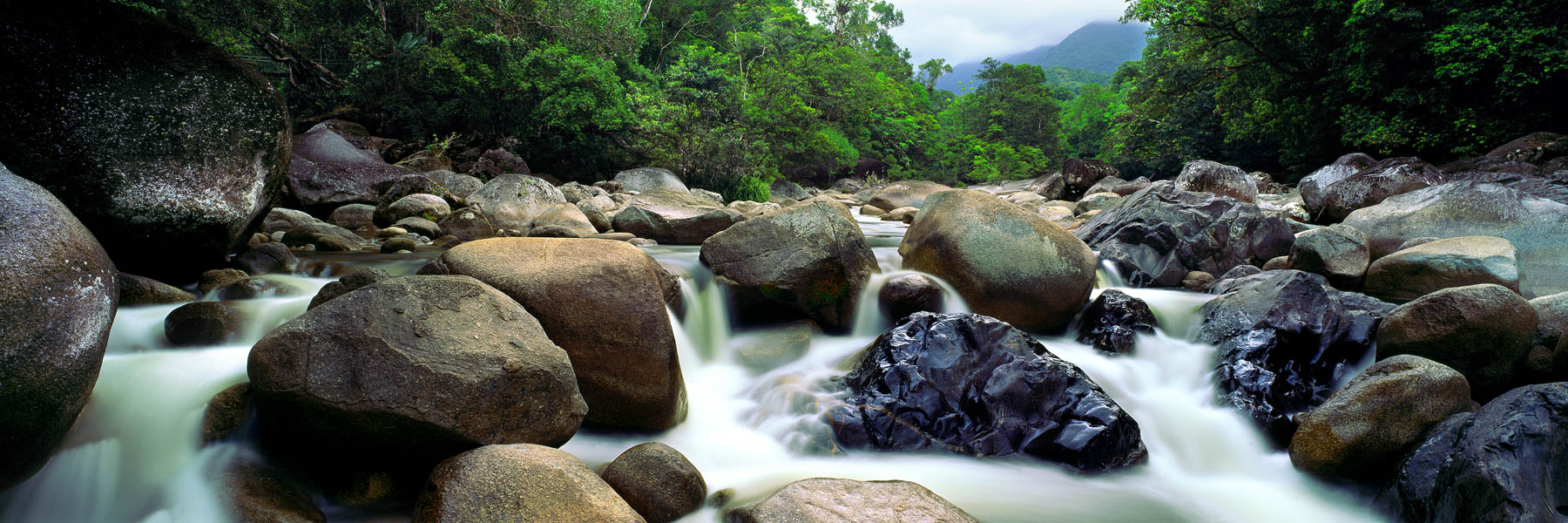 Mossman River flowing over boulders, through the rainforest, Qld, Australia.