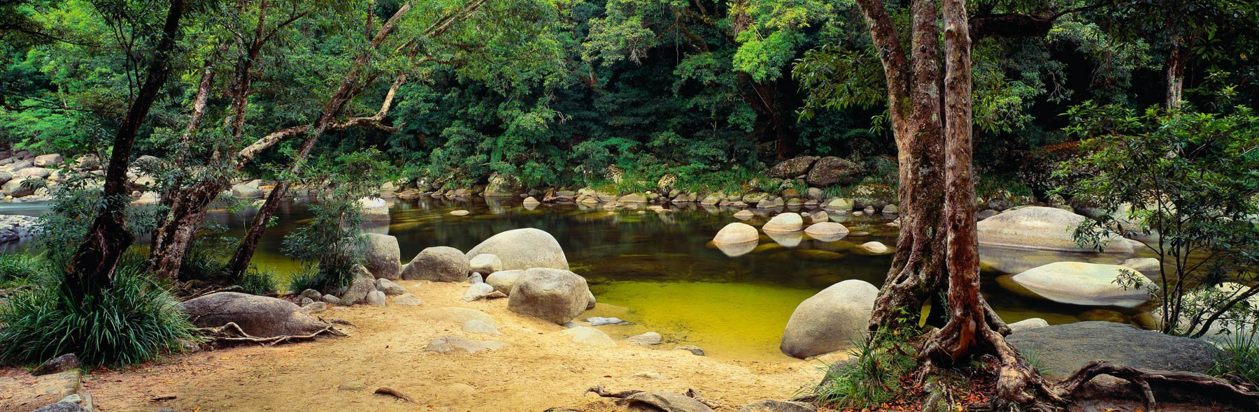 The Mossman River tumbling gently over boulders into a refreshing swimming hole, Qld, Australia.