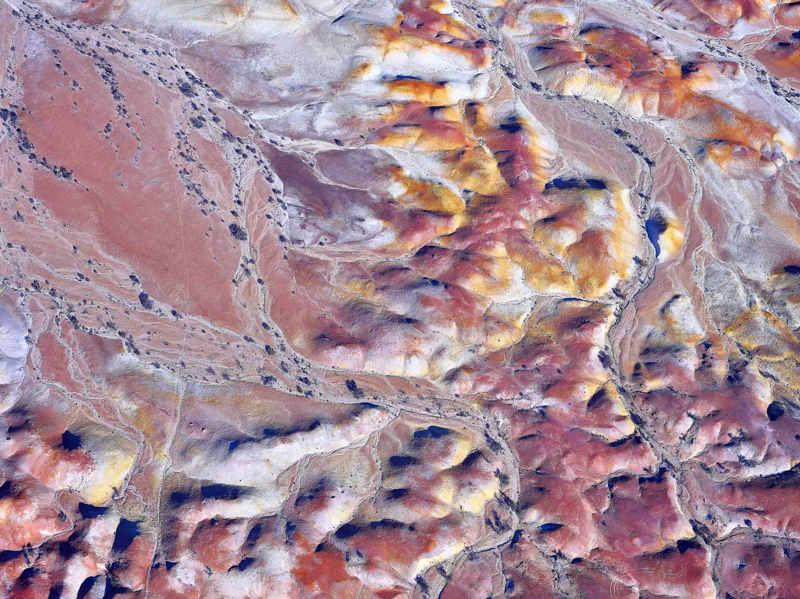 Aerial photo of dry creek beds winding through Anna Creek Painted Hills, South Australia