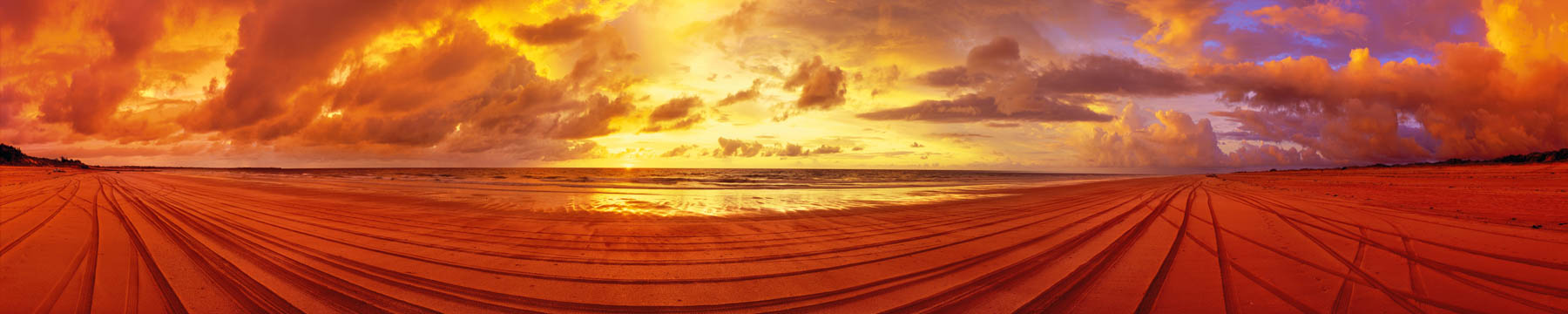 A rich, red sunset lights up the sand and sky at Cable Beach, Broome, WA, Australia.
