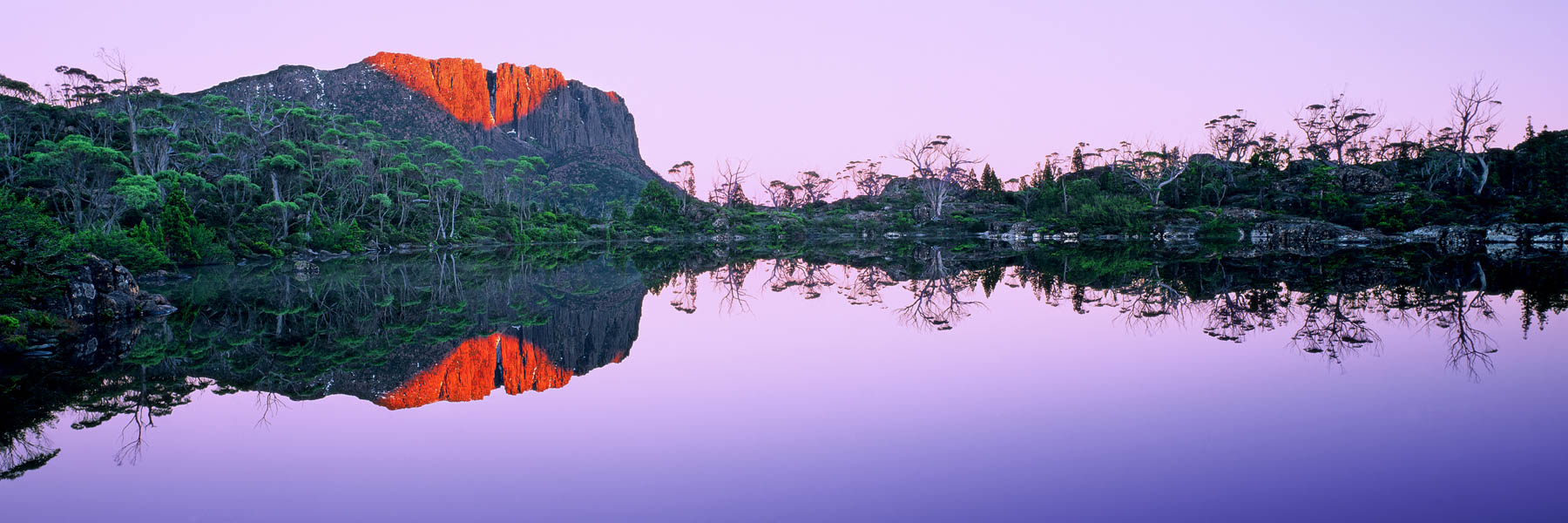 The rising sun painting the rock formations behind Lake Elysia with a bright red-gold, Tasmania, Australia.