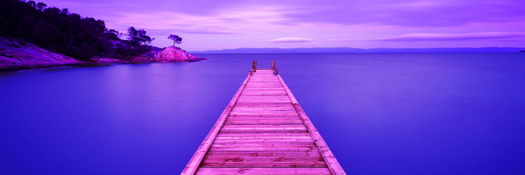 A serene pastel sunrise over Coleas Bay, Tasmania, Australia.