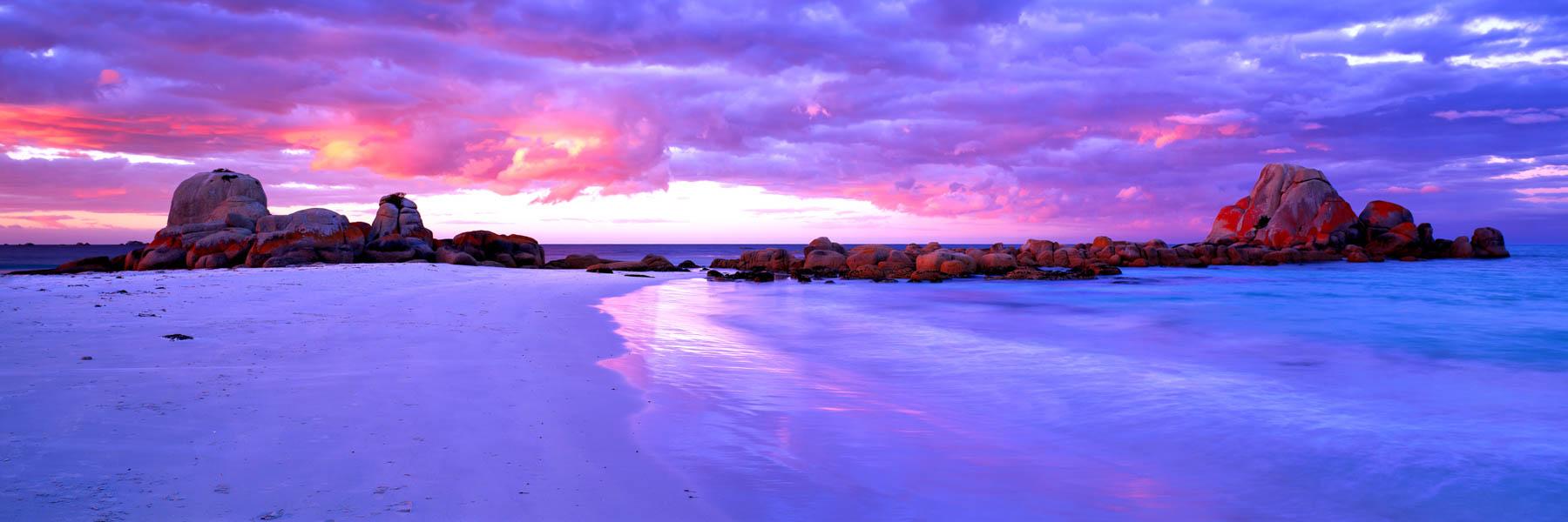 A pastel sunrise lighting up the rocks and sky at Picnic Rocks, Bay of Fires, Tasmania, Australia.