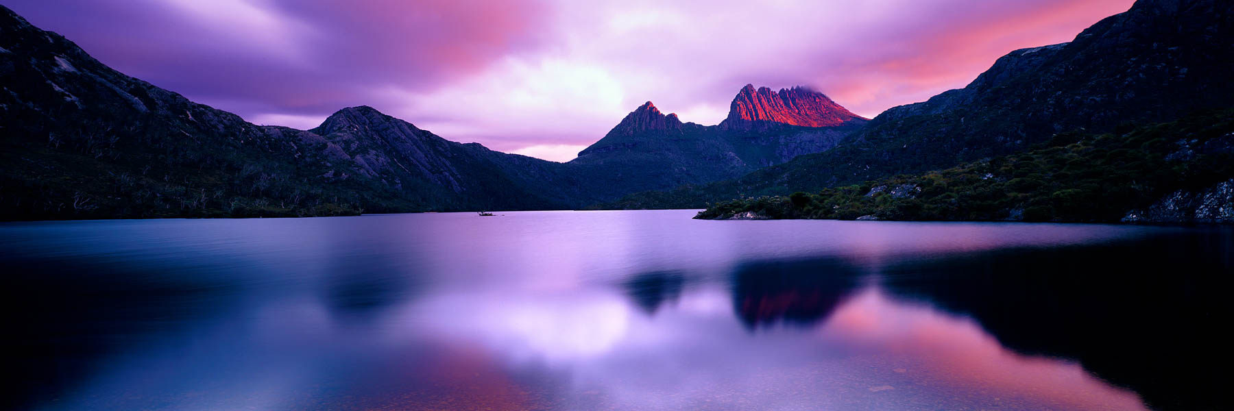 A shaft of dawn sunlight pierces the clouds above Dove Lake, Cradle Mountain, Tasmania, Australia.