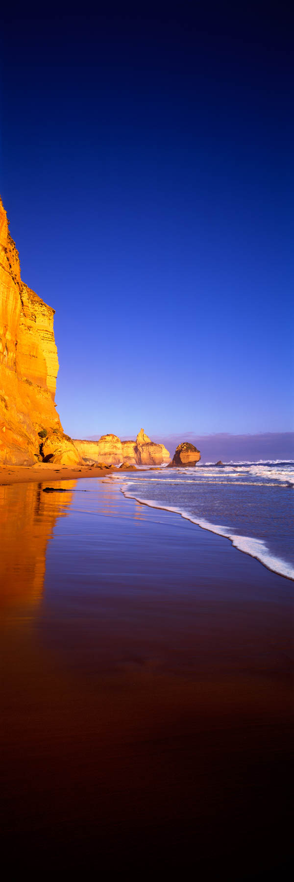 A vertical view of The Twelve Apostles from the beach on a beautiful, calm day.