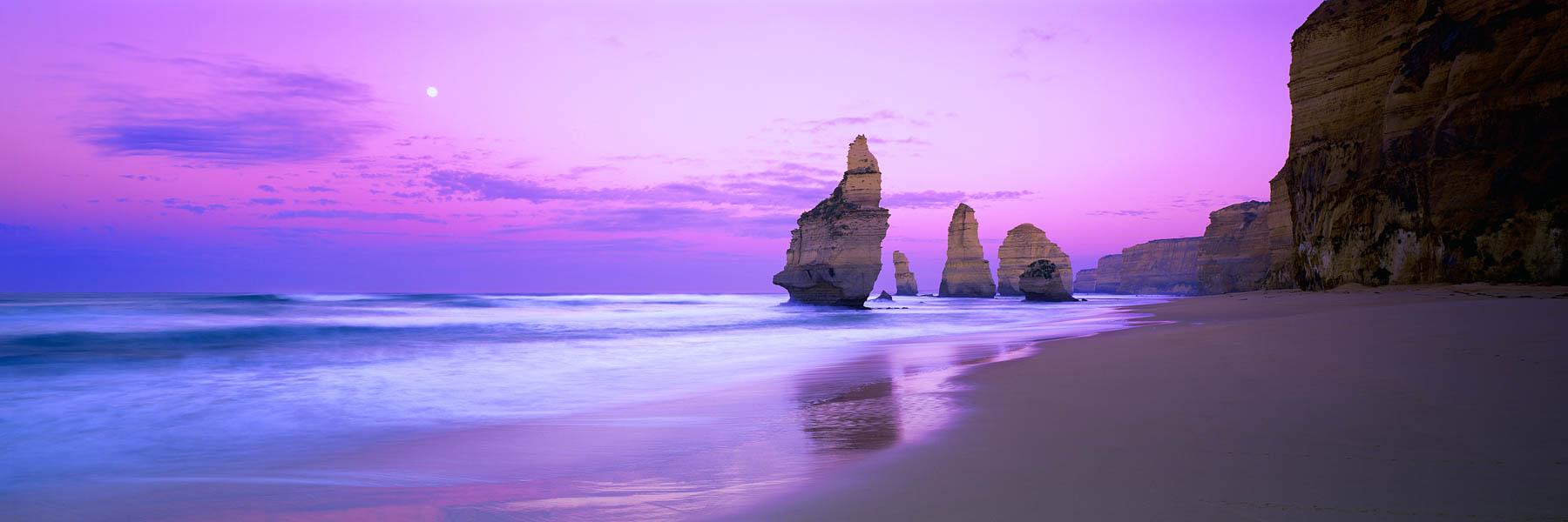 A full moon setting into a pastel sunrise over The Twelve Apostles, Victoria, Australia.