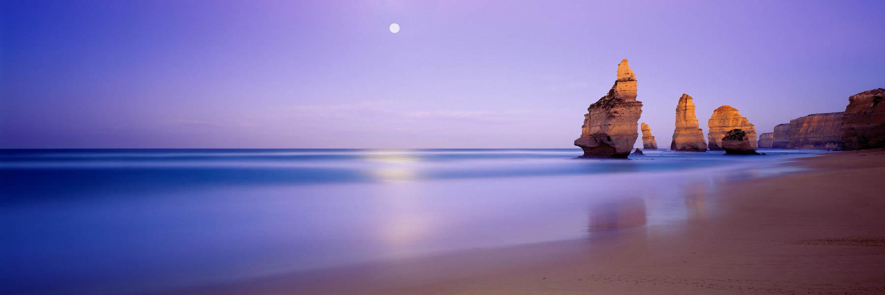 A full moon at sunrise over The Twelve Apostles, Victoria, Australia.