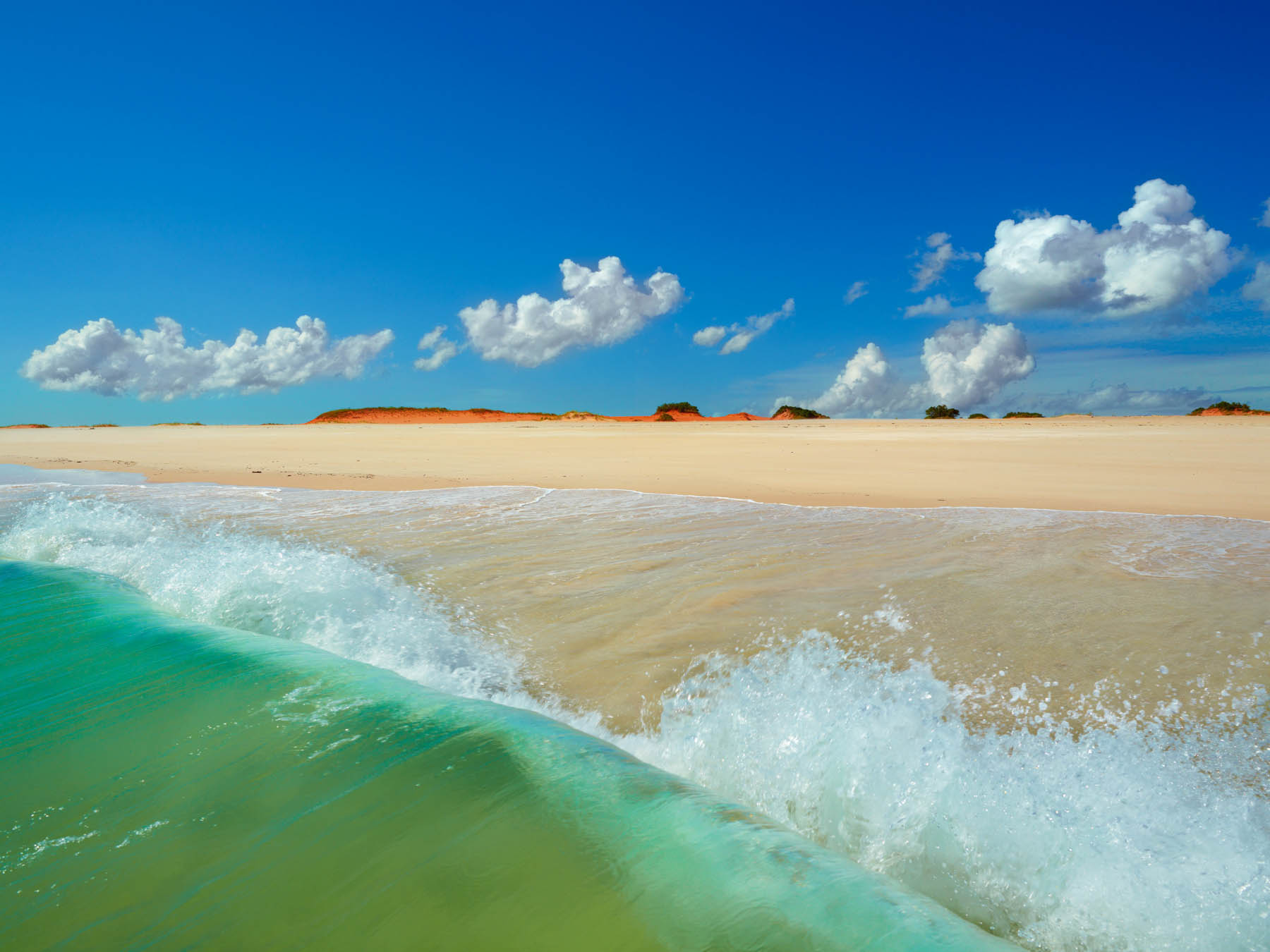 Turquoise waves gently breaking on the pure white sand of Cape Leveque, Kimberleys, WA, Australia.