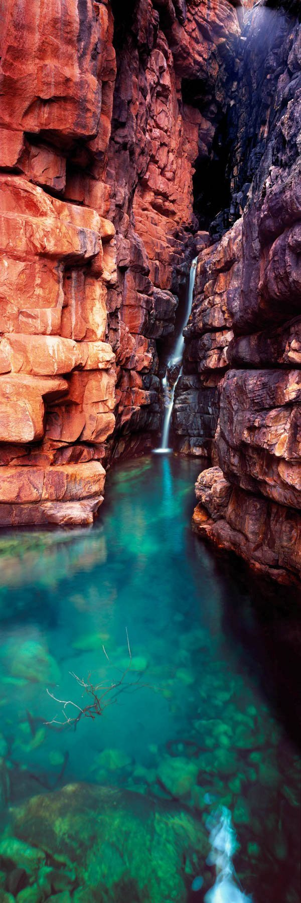 Sparkling fresh water flows down into a crystal clear pool in The Kimberleys, WA, Australia.